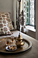 A Moroccan brass teapot and glasses sits on a tray on the double bed.