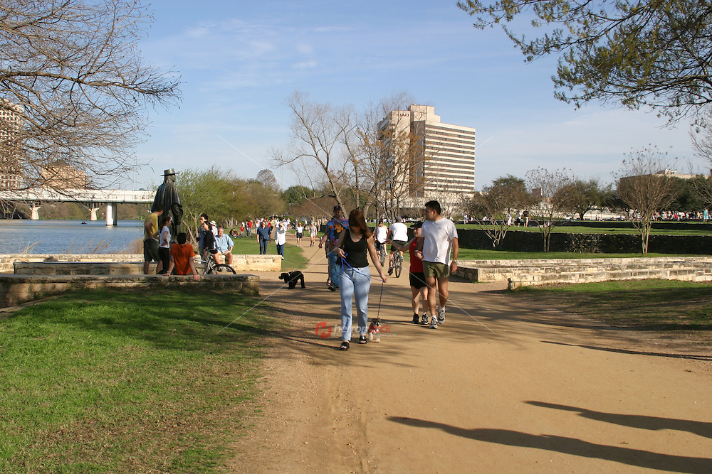 Dog walkers and tourist spend the afternoon visiting the SRV Stevie Ray Vaughn Memorial Statue at Auditorium Shores on Town Lake.