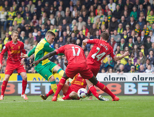 20.04.2014.  Norwich, England. Gary Hooper of Norwich City has his shot blocked by the Liverpool defenders during the Barclays Premier League match between Norwich City and Liverpool from Carrow Road.