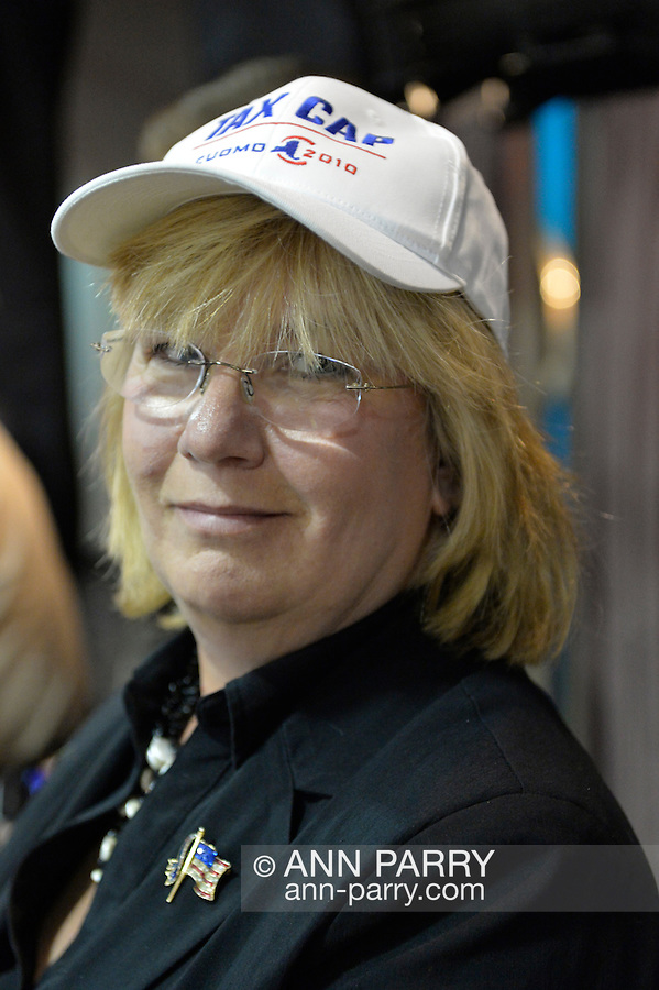 Seaford, New York, USA. 3rd June 2015. CLAUDIA BORECKY, of Merrick, the Democratic candidate for Legislator of Nassau County Legislature District 19, wears a cap with TAX CAP CUOMO 2010 written on it at an event supporting extension of the NY Property Tax Cap. At the bi-partisan Press Conference at Knights of Columbus Hall, over a hundred area residents and officials, and the governor, urged extending the property tax cap before the state legislative session ends on June 17. The NY Property Tax Cap is set to expire June 2016, but is legally linked to NYC rent-control regulations set to expire this month.