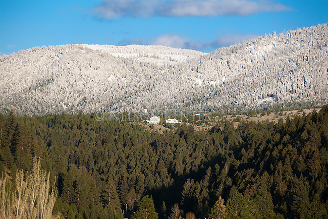 A house on a ridge above Missoula, Montana with a layer of late spring snow on the higher hills