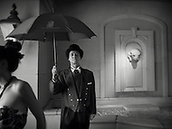 A bellhop at an upscale New Orleans hotel stands outside with an umbrella.