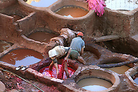 High angle view of reflections in the dyeing pits where men are working, Chouara tannery, Fez, Morocco, pictured on February 23, 2009 at sunset. The Chouara tannery is the largest of the four ancient tanneries in the Medina of Fez where the traditional work of the tanners has remained unchanged since the 14th century. It is composed of numerous dried-earth pits where raw skins are treated, pounded, scraped and dyed. Tanners work in vats filled with various coloured liquid dyes derived from plant sources. Colours change every two weeks, poppy flower for red, mint for green, indigo for blue, chedar tree for brown and saffron for yellow. Fez, Morocco's second largest city, and one of the four imperial cities, was founded in 789 by Idris I on the banks of the River Fez. The oldest university in the world is here and the city is still the Moroccan cultural and spiritual centre. Fez has three sectors: the oldest part, the walled city of Fes-el-Bali, houses Morocco's largest medina and is a UNESCO World Heritage Site;  Fes-el-Jedid was founded in 1244 as a new capital by the Merenid dynasty, and contains the Mellah, or Jewish quarter; Ville Nouvelle was built by the French who took over most of Morocco in 1912 and transferred the capital to Rabat. Picture by Manuel Cohen.