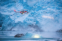 A helicopter flown by operator Lufttransport for the Govenor of Svalbard (Sysselmannen), flying in front of the Nordenskiold glacier. <br />