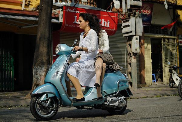 Asia, Vietnam, Hanoi. Hanoi old quarter. Two young dressy vietnamese women riding a Vespa motorbike through Hanoi.