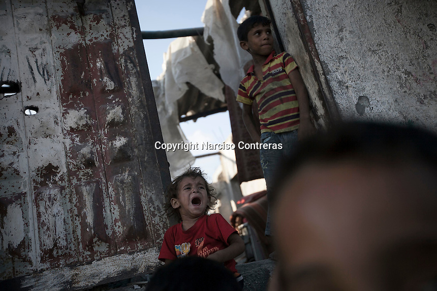 """In this Saturday, Aug. 16, 2014 photo, Palestinian children are seen at the entrance of their house after it was damaged by artillery shelling during the """"Protective Edge"""" Israeli military operation in Beit Hanoun neighborhood in Gaza City. After a five days truce was declared on 13th August between Hamas and Israel, civilian population went back to what remains from their houses and goods in Gaza Strip. (Photo/Narciso Contreras)"""
