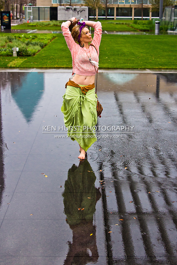 Beautiful Bohemian woman dressed in colorful clothing dancing in a reflecting pool.