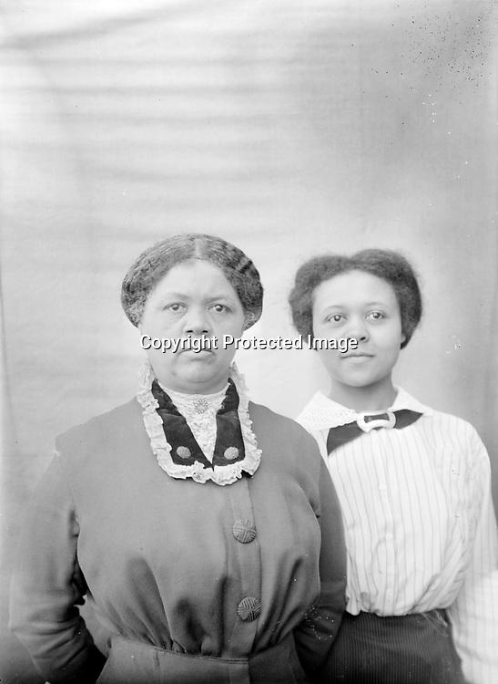 FRANCES HILL AND MATRON. Frances Hill (1904-1932) stands demurely behind an older woman--perhaps her mother? Hill boarded with John C. Galbreath's family even before she graduated from Lincoln High School in 1924 and as late as 1929. Galbreath also provided her grave at Wyuka Cemetery upon her young death in 1932. (Frances Hill appears in other images)<br /> <br /> The 1920 census shows Aaron Douglas, 21 year old University student, was a roomer in the household of Ben. F. &amp; Lottie Corneal. Ben was head of the waiters club of Lincoln; a second roomer was a barber. They resided at 524 N. 9th--a couple of blocks south of Mamie Griffin's house at 915 U. The Corneals next door neighbors were John and Mable Galbreath at 524 N. 9th. John was sometimes a waiter; in 1920 he was listed as operating a restaurant. John and Mable also had a roomer, as well as a stepdaughter--15 year old Frances Hill. <br /> <br /> Photographs taken on black and white glass negatives by African American photographer(s) John Johnson and Earl McWilliams from 1910 to 1925 in Lincoln, Nebraska. Douglas Keister has 280 5x7 glass negatives taken by these photographers. Larger scans available on request.