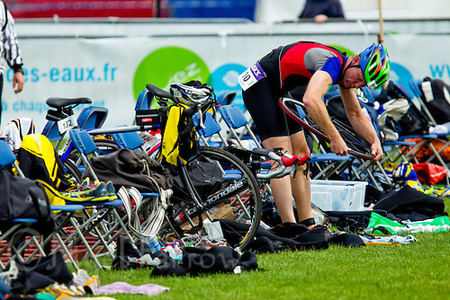 13 JUN 2010 - BEAUVAIS, FRA - A competitor repairs a puncture in transition before heading to the bike course during the Beauvais Triathlon (PHOTO (C) NIGEL FARROW)