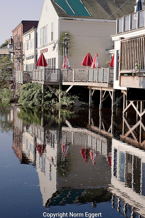 Reflections in the Water of red umbrellas and buildings in Camden, Maine