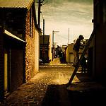 Man on ladder beside buildings