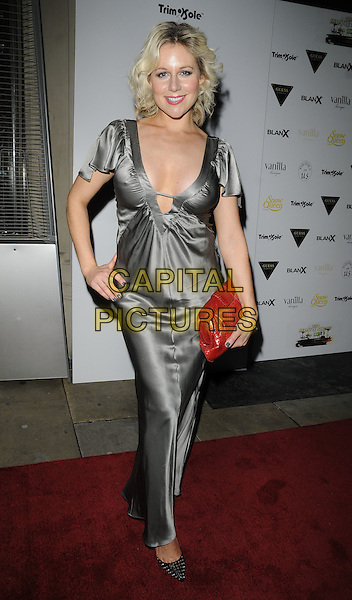 ABI TITMUSS .ITV At The Movies Oscars Party, London,  Sanctum Soho Hotel, London, England, UK, February 27th 2011..full length silver long maxi silk satin dress cleavage red clutch bag hand on hip .CAP/CAN.©Can Nguyen/Capital Pictures.