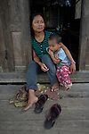 A woman and her child sit in the doorway of their home in Tuingo, an ethnic Chin village in Myanmar.