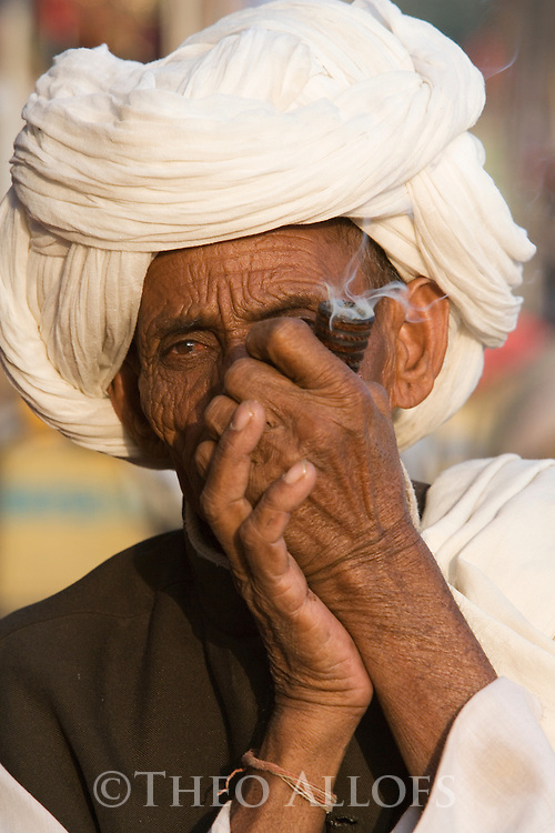 Rajasthani man smoking pipe at Pushkar camel fair; .The annual Pushkar camel fair is one of the main tourist attractions in India, Pushkar, Rajasthan, India --- Model Released