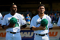 Augusta GreenJackets Franklin Van Gurp (10) and Jesus Tona (29) during the national anthem before a South Atlantic League game against the Lexington Legends on April 30, 2019 at SRP Park in Augusta, Georgia.  Augusta defeated Lexington 5-1.  (Mike Janes/Four Seam Images)