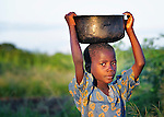 """A girl carries grain on her head to get it milled in Dickson, a village in southern Malawi that has been hard hit by drought in recent years, leading to chronic food insecurity, especially during the """"hunger season,"""" when farmers are waiting for the harvest."""