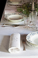 Detail of a table dressed laid for Christmas dinner with blue and white china and crisp monogrammed linen napkins