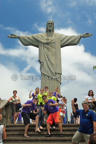 Brazil, Rio de Janeiro: Group of  tourists posing for a photograph in front of the iconic Christo Redentor statue on Corcovado. --- Info: Christ the Redeemer (Portuguese: O Cristo Redentor) is a statue of Jesus Christ in Rio de Janeiro, Brazil. The monument, considered the largest art deco statue in the world, stands 39.6 metres tall (including its 9.5 metre pedestal) and 30 metres wide; and is located at the peak of the 700 metres Corcovado mountain in the Tijuca Forest National Park overlooking Rio's city. The idea for erecting a large statue atop Corcovadogoes back to the mid 1850s, but construction was finally undertaken between 1922 and 1931. The monument was opened on October 12, 1931. A symbol of Christianity, the statue has become an icon of Rio and Brazil. --- No signed releases available.
