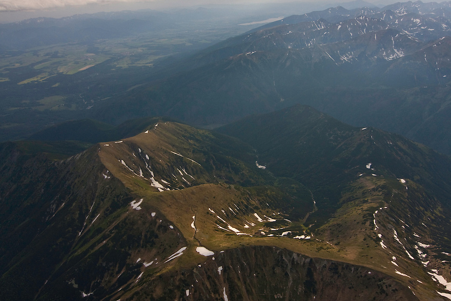 Aerial view of the Liptovske kopi, the Ticha valley and the Western Tatras on the right. On the background the valley of Liptov and the Low Tatras mountain range in the background. Western Tatras, Slovakia. June 2009. Mission: Ticha