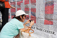 A woman photographs a name on the list of those who perished in the 9/11 terrorist attack of the World Trade Center.  The list is posted on Greenwich Street across from the entrance to the National September 11 Memorial.