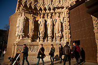 Statues at the entrance to the cathedral of Notre-Dame de Reims, Reims, France, 11 November 2015. The Smiling Angel (far right) is the most famous of the cathedrals statues. She was hit by debris from a fire after being shelled by German artillery at the beginning of World War I and lost her head, which has since been restored. The statues are reddish in colour due to the molten lead that poured over them during the fire as the roof was destroyed.