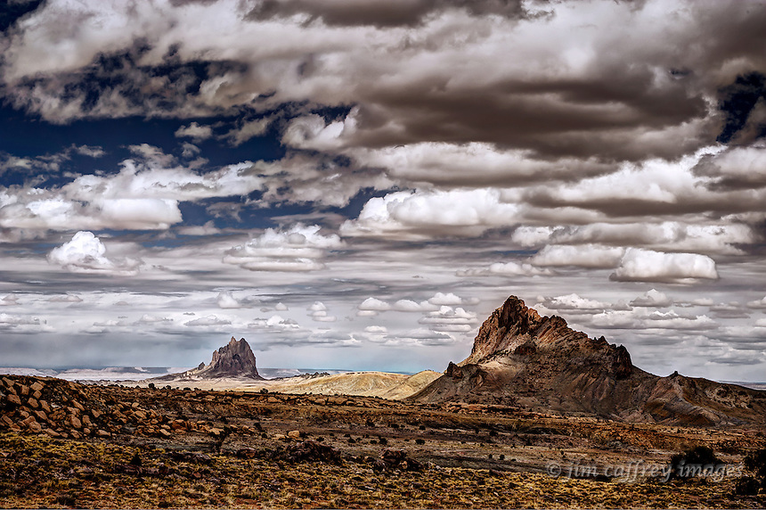 Mitten Rock in the foreground and Shiprock in the distance under a stormy sky.