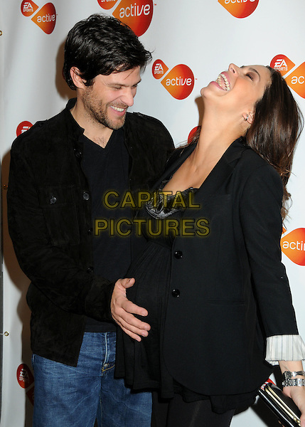 "GREG VAUGHAN & TOURIYA HAOUD.EA Sports Active and Nancy O'Dell Presents ""Active For Life"" Event and Charity Auction Benefiting March Of Dimes held at 8443 Warner Studios, Culver City, California, USA..half length married husband wife black top jacket profile looking up laughing hand on stomach pregnant .CAP/ADM/BP.©Byron Purvis/AdMedia/Capital Pictures."