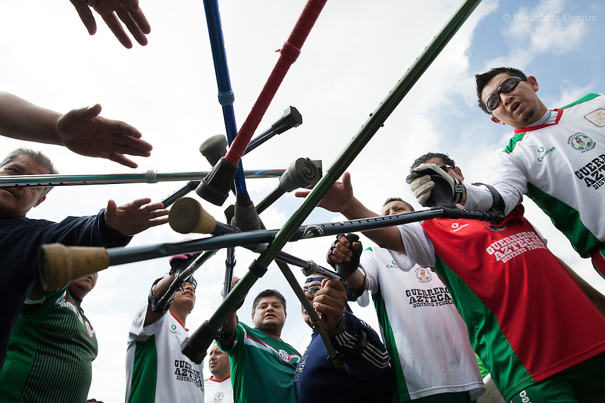 "Players from Guerreros Aztecas join their crutches together before playing a match against Los Dragones (""the Dragons"")  in Deportivo Tlalli II in Talnepantla, Mexico on September 27, 2014. Guerreros Aztecas (""Aztec Warriors"") is Mexico City's first amputee football team. Founded in July 2013 by five volunteers, they now have 23 players, seven of them have made the national team's shortlist to represent Mexico at this year's Amputee Soccer World Cup in Sinaloa this December. The team trains twice a week for weekend games with other teams. No prostheses are used, so field players missing a lower extremity can only play using crutches. Those missing an upper extremity play as goalkeepers. The teams play six per side with unlimited substitutions. Each half lasts 25 minutes. The causes of the amputations range from accidents to medical interventions – none of which have stopped the Guerreros Aztecas from continuing to play. The players' age, backgrounds and professions cover the full sweep of Mexican society, and they are united by the will to keep their heads held high in a country where discrimination against the disabled remains widespread. (Photo by Bénédicte Desrus)"