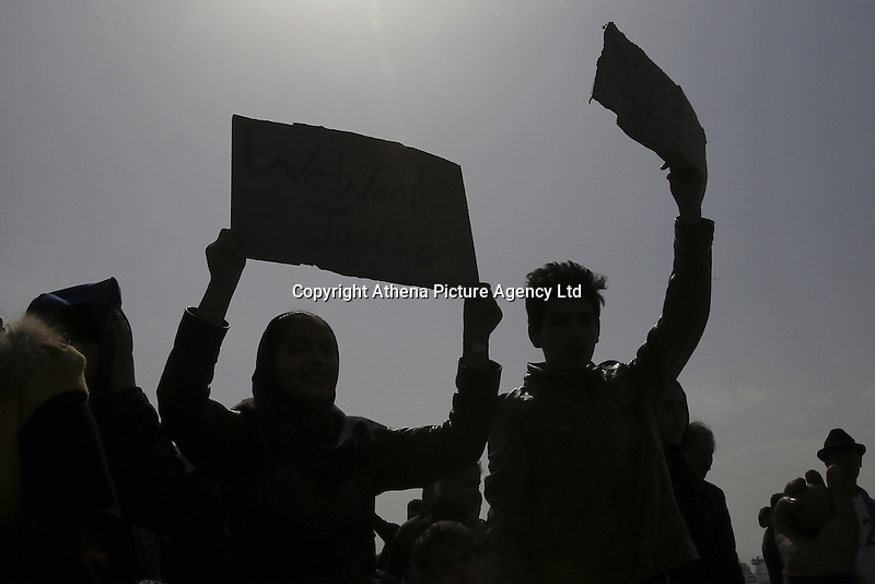 Pictured: Protesters with placards marching next to a ship in Piraeus port Tuesday 08 March 2016<br /> Re: Afghan migrants hold a protest at Piraeus port, near Athens, Greece.