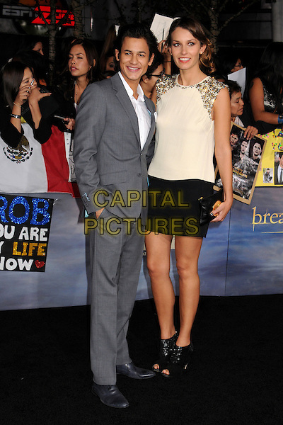 "Bronson Pelletier & guest.""The Twilight Saga: Breaking Dawn - Part 2"" Los Angeles Premiere held at Nokia Theatre L.A. Live, Los Angeles, California, USA..November 12th, 2012.full length suit grey gray white top black skirt open toe ankle boots  .CAP/ADM/BP.©Byron Purvis/AdMedia/Capital Pictures."