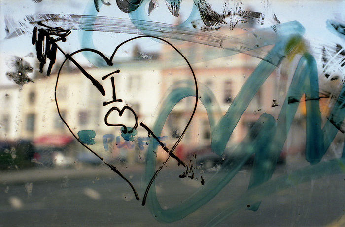 Graffiti written and scratched onto a bus shelter window, Brighton. 2001.