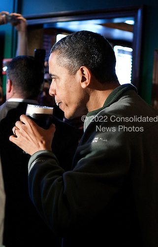 United States President Barack Obama takes a sip of Guinness beer as he visits a bar in celebration of St. Patrick's day at the Dubliner Restaurant and Pub on March 17, 2012 in Washington, DC. Next week, Obama and Vice President Biden will meet the Irish Prime Minister Enda Kenny and attend a St. Patrick's Day lunch at the Capitol. .Credit: Joshua Roberts / Pool via CNP