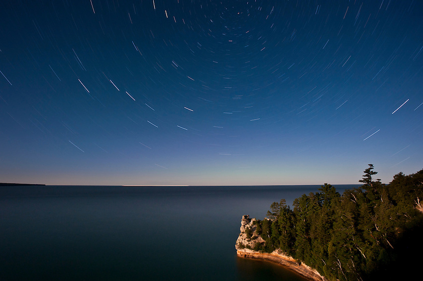 Star trails in the night sky over Miners Castle at Pictured Rocks National Lakeshore in Munising Michigan Upper Peninsula.