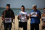 Wounded Palestinians, who were lose their legs during the clashes with Israeli troops, hold placards during a protest calling to boycott Puma sport company, on the beach of Gaza city on May 29, 2019. Puma is the main sponsor of the Israel Football Association (IFA), which includes teams in Israel's illegal settlements on occupied Palestinian. Photo by Mahmoud Ajjour