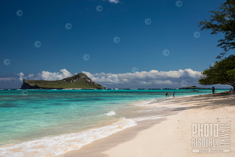 Beachgoers enjoy the white sand and clear waters of Waimanalo Beach and Bay, with Manana and Kaohikaipu (or Rabbit and Bird) Islands in the distance, Windward O'ahu.
