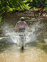 NWA Democrat-Gazette/BEN GOFF @NWABENGOFF<br /> Racers ford a creek Sunday, July 16, 2017, during cross country races on the final day of the 19th annual Fat Tire Festival at Lake Leatherwood City Park in Eureka Springs.