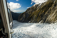 Downstream view from helicopter into valley across crevasses on Franz Josef Glacier and toward Tasman Sea on horizon, Westland Tai Poutini National Park, West Coast, UNESCO World Heritage Area, New Zealand, NZ