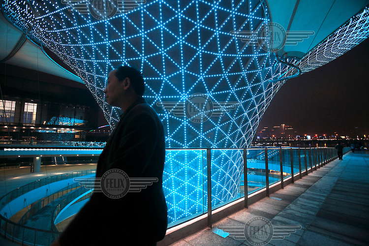 Visitors walking past the illuminated funnel-like structures of Sunny Valley during the first day of the trial run for the 2010 World Expo. The structures are designed to bring natural light into areas below ground level.