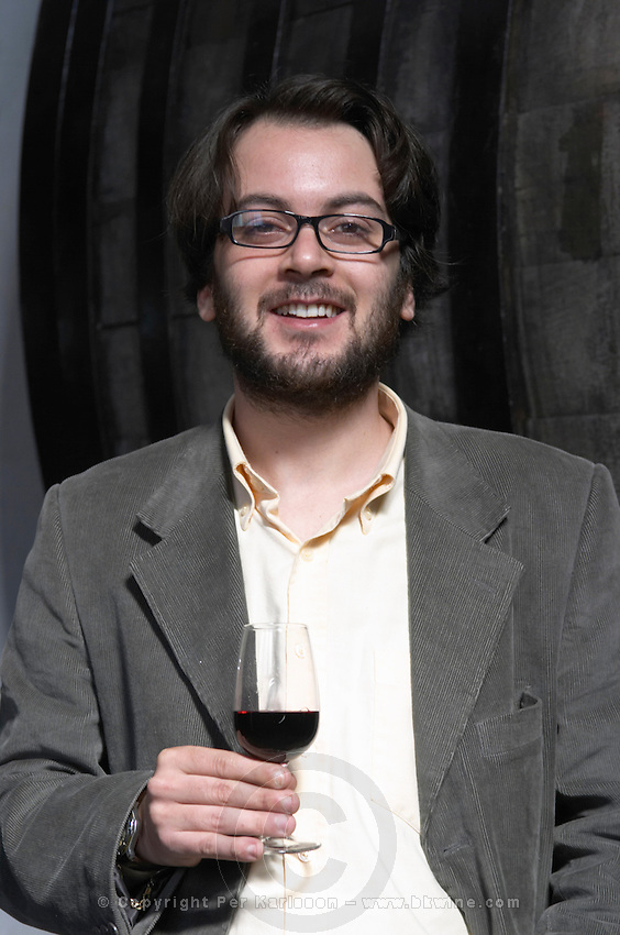 Mr Mendez co-owner and son of Marta Mendez winemaker holding a glass of wine in the winery in front of an old oak barrel. Bodega Plaza Vidiella Winery, Las Brujas, Canelones, Uruguay, South America
