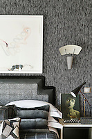 The bedroom is decorated in monochrome shades with soft textures such as the tweed wall covering. The bed headboard is edged with leather and wall light hangs above a bedside table.