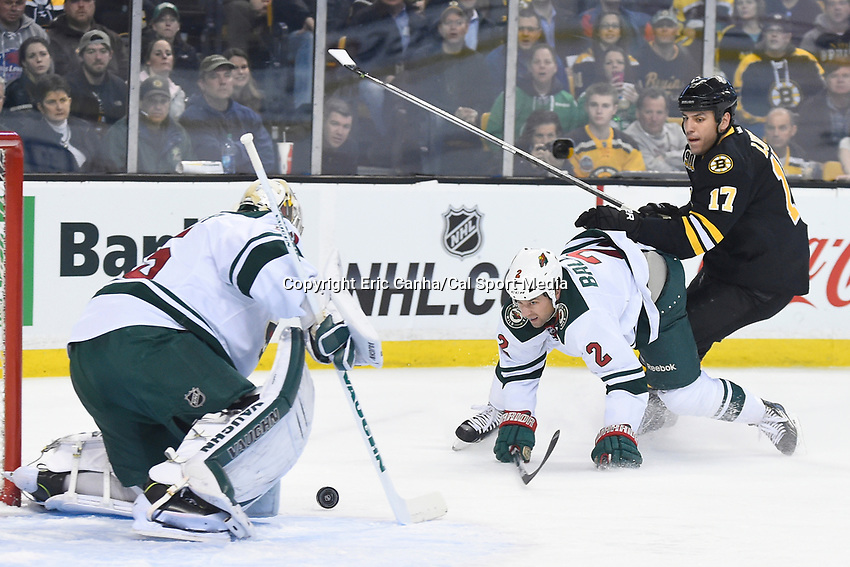 March 17, 2014 - Boston, Massachusetts , U.S. - Minnesota Wild goalie Darcy Kuemper (35) makes a save as Boston Bruins left wing Milan Lucic (17) and defenseman Keith Ballard (2) battle in front of the net during the NHL game between the Minnesota Wild and the Boston Bruins held at TD Garden in Boston Massachusetts.  Eric Canha/CSM