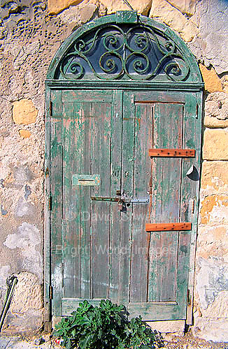 old faded green door in limestone wall Valletta Malta