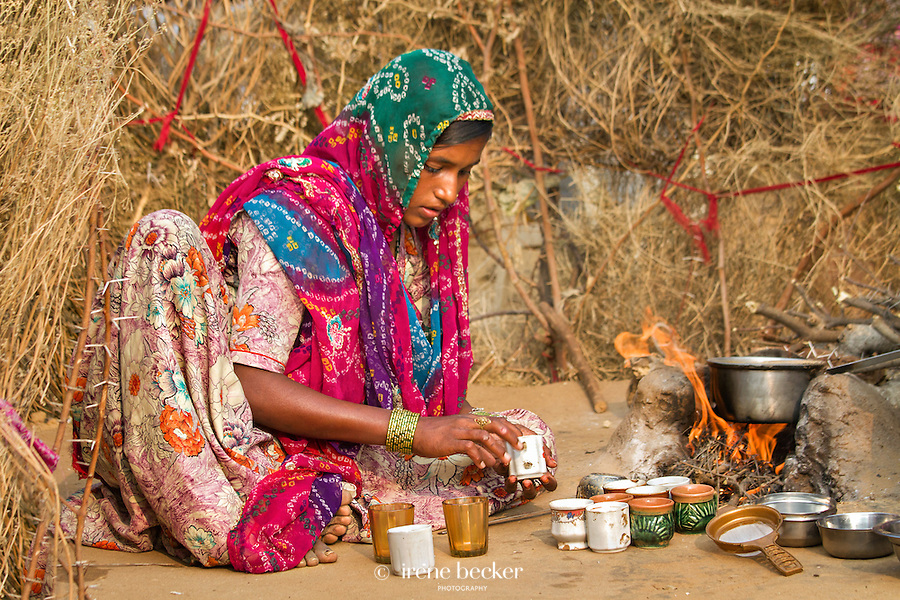 Making Chai. Indian teenage girl preparing chai (masala tea) on traditional chulha (stove). Pushkar, Rajashan, India.