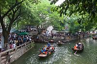 Suzhou, Jiangsu, China.  Chinese Tourists Boating on a Canal in Tongli Ancient Town near Suzhou, a popular weekend tourist destination.