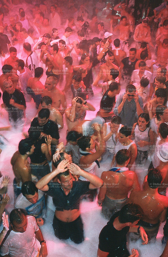 Spain. Ibiza in the Balearic islands. Ibiza. Night life. Disco Amnesia. The crowd dances on the sound of the techno music during the lather of soap night event.  © 1999 Didier Ruef