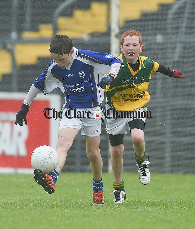 Paddy Hassett of Parteen in action against Fiachra Malone of Killimer during the U-12 football finals in Cusack park. Photograph by John Kelly.
