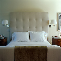In an East Hampton bedroom a large retro padded headboard creates an air of comfort