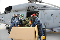 Helicopter Antisubmarine Squadron 14 sailors load humanitarian supplies onboard an SH-60F helicopter. HS- 14 is conducting humanitarian assistance and search-and-rescue operations on the eastern coast of Japan in support of Operation Tomodachi.