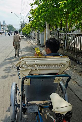 Asia, Vietnam, Nha Trang. Cyclo (cycle rickshaw) driver waiting for customers.