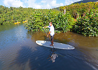 Caucasian male stand up paddleboarding on the Hanalei River, Kaua'i